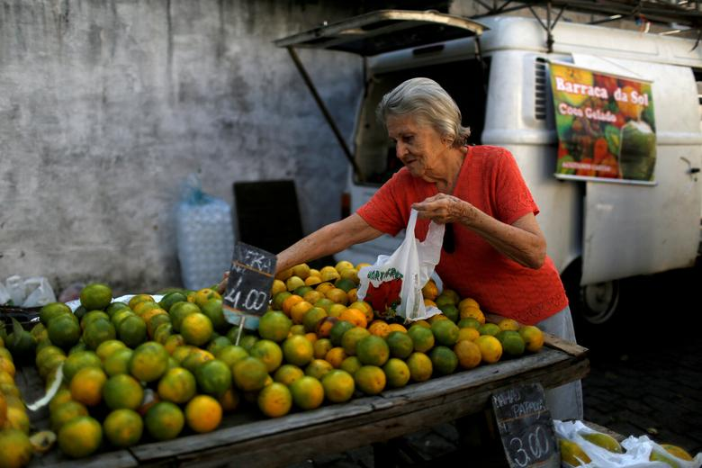FILE PHOTO -  A customer selects oranges at a street market in Rio de Janeiro, Brazil, May 6, 2016. REUTERS/Pilar Olivares/File Photo
