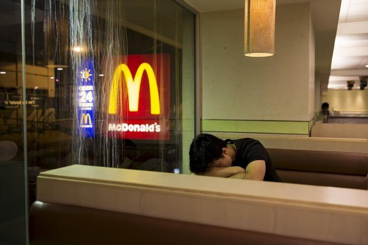 A man sleeps at a 24-hour McDonald's restaurant in Hong Kong, China November 10, 2015. REUTERS/Tyrone Siu