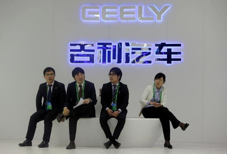 Staff members sit in front of a Geely signage at Auto China 2014 in Beijing April 20, 2014. REUTERS/Jason Lee/File photo