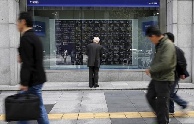 2月22日、寄り付きの東京株式市場で日経平均は前日比37円78銭高の1万9419円22銭となり、小幅続伸して始まった。写真は株価ボードを眺める男性、都内で昨年4月撮影(2017年 ロイター/Toru Hanai)