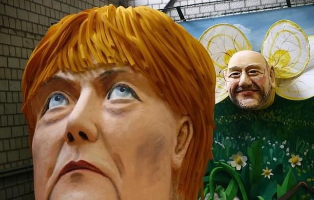Papier mache caricatures depicting German Chancellor Angela Merkel and SPD challenger Martin Schulz are pictured during preparations for the upcoming Rose Monday carnival parade in Cologne, Germany, February 21, 2017.     REUTERS/Wolfgang Rattay