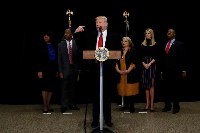 U.S. President Donald Trump is flanked by Ben Carson (2nd L), his nominee to lead the Department of Housing and Urban Development (HUD), Carson's wife, Candy Carson (L), Martin Luther King Jr's niece Alveda KIng (3rd R), Trump's daughter Ivanka Trump (2nd R), and U.S. Senator Tim Scott (R-SC) (R) as he delivers remarks after visiting the National Museum of African American History and Culture on the National Mall in Washington, U.S., February 21, 2017. REUTERS/Jonathan Ernst
