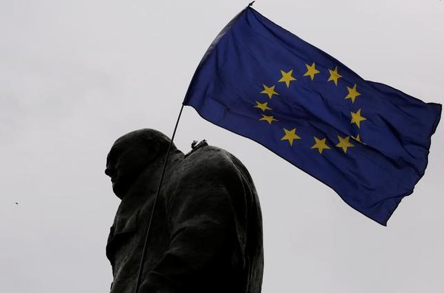2月23日、欧州中央銀行(ECB)のプラート専務理事は英国の欧州連合(EU)離脱は貿易に大きな影響を及ぼすとの見方を示し、状況は「かなり急速に悪化する」可能性もあることから、盲目的に楽観視すべきでないと警告した。写真は英国のEU離脱に抗議するデモ参加者らが掲げたEUの旗とチャーチルの像。ロンドンで2016年9月撮影(2017年 ロイター/Luke MacGregor)
