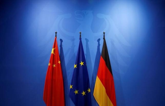 2月24日、ドイツ連邦統計庁のデータによると、昨年の同国最大の貿易相手国に中国が浮上した。写真は左から中国、EU、ドイツの国旗、ベルリンで昨年11月撮影(2017年 ロイター/Fabrizio Bensch)
