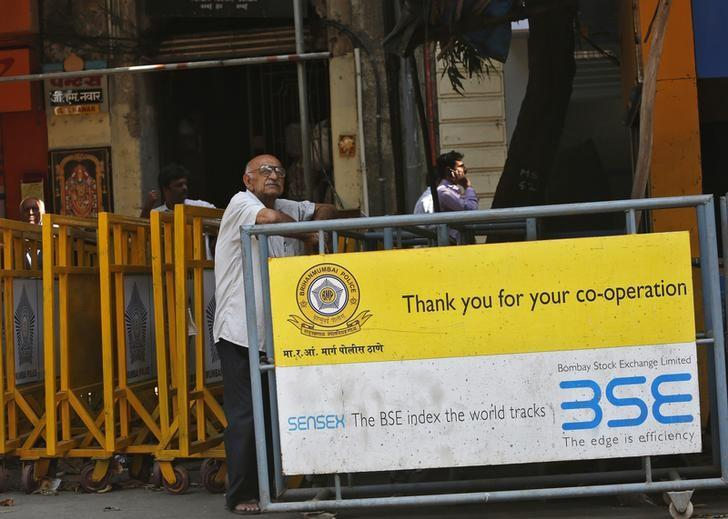 A man looks at a screen across the road displaying the Sensex on the facade of the Bombay Stock Exchange (BSE) building in Mumbai February 6, 2014. REUTERS/Mansi Thapliyal/File Photo