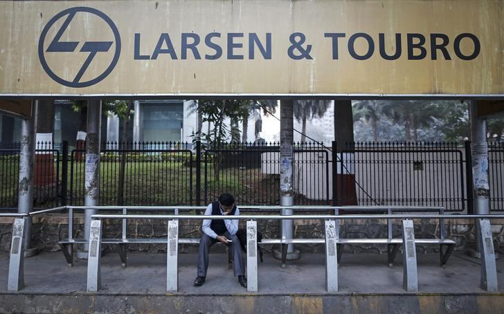 A man waits at a bus-stop with an advertisement of Larsen & Toubro outside the company's manufacturing unit in Mumbai January 22, 2014. REUTERS/Danish Siddiqui/File Photo