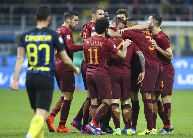 2月26日、サッカーのイタリア・セリエAは各地で試合を行い、長友佑都所属のインテルはホームで2位ローマに1─3で敗れた。長友はベンチ入りしたものの、出番はなかった。写真はゴールを喜ぶローマの選手たち(2017年 ロイター/Stefano Rellandini)