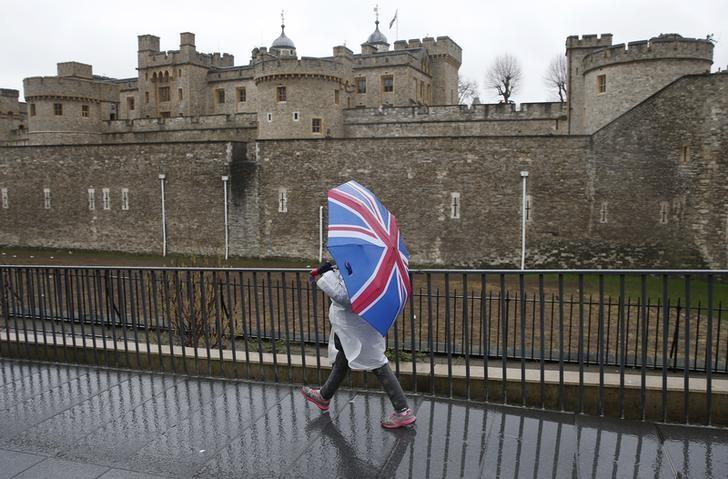 A tourist carrying a Union Flag umbrella walks in the rain during a spell of wet weather, next to The Tower of London, in London, Britain January 15, 2017.  REUTERS/Peter Nicholls