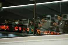 Visitors use their mobile phones before a ceremony marking the end of trading in 2016 at the Tokyo Stock Exchange (TSE) in Tokyo, Japan December 30, 2016. REUTERS/Toru Hanai