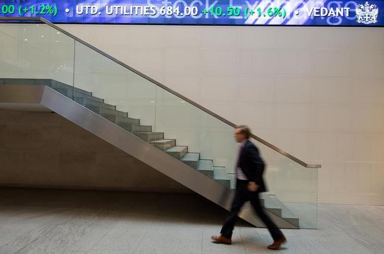 A man walks under an electronic information board at the London Stock Exchange in the City of London January 2, 2013.   REUTERS/Paul Hackett