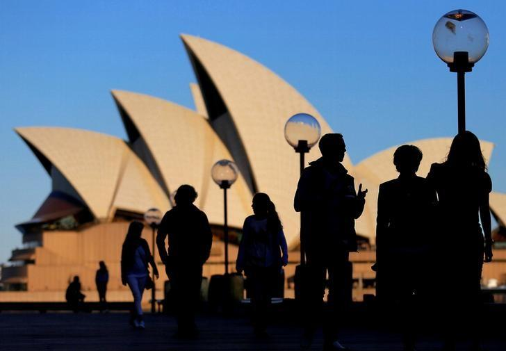 People are silhouetted against the Sydney Opera House at sunset in Australia, November 2, 2016.  REUTERS/Steven Saphore/Files