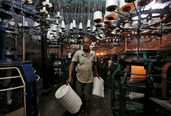 An employee carries cloth rolls inside an undergarment factory in Kolkata, India, February 1, 2017. REUTERS/Rupak De Chowdhuri