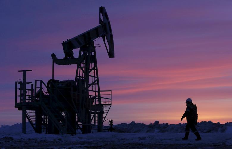 A worker walks past a pump jack on an oil field owned by Bashneft in Bashkortostan, Russia, January 28, 2015.      REUTERS/Sergei Karpukhin/File Photo