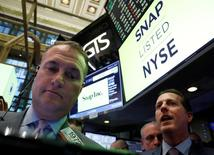 Operadores revisan el precio de la acción de Snap tras su debut en la bolsa de Nueva York.  Las acciones de la empresa de tecnología volvieron a dispararse el viernes y ganaron un 10,7 por ciento, mientras que el mercado bursátil de Estados Unidos cerró plano y anotó su sexta semana consecutiva de ganancias. REUTERS/Brendan McDermid