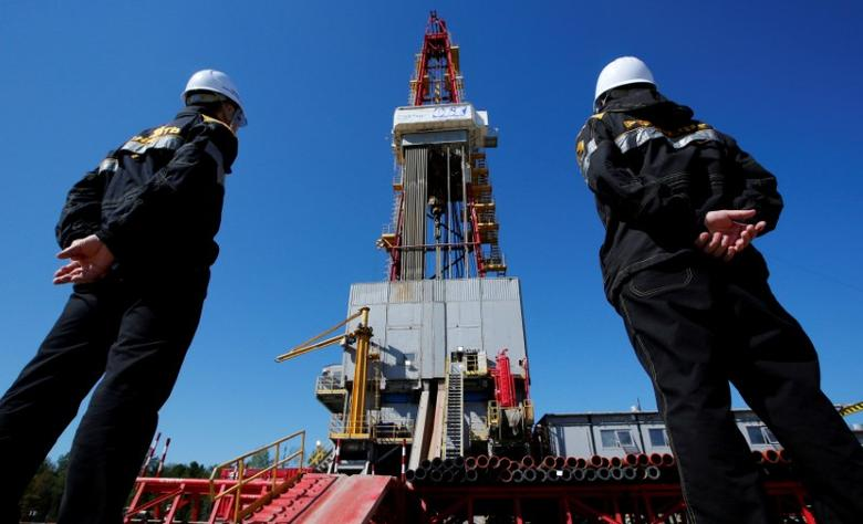 Workers look at a drilling rig of the Rosneft-owned Prirazlomnoye oil field outside Nefteyugansk, Russia, August 4, 2016. REUTERS/Sergei Karpukhin/File Photo