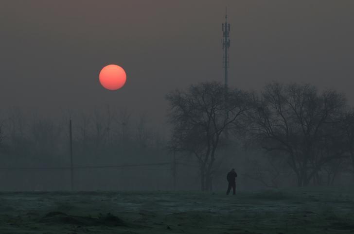2016年12月19日,北京发布空气污染红色预警,一名男子在清晨外出。REUTERS/Jason Lee