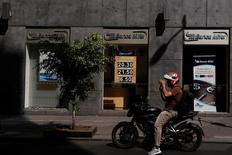 Un motociclista pasa frente a una casa de cambio de una sucursal del banco Mifel en Ciudad de México. Las paridades cambiarias de Latinoamérica seguirían en equilibrio esta semana gracias a diferentes iniciativas de los gobiernos de la región, muy activos para impedir que los mercados financieros locales sufran por los crecientes riesgos externos y los problemas internos. REUTERS/Carlos Jasso