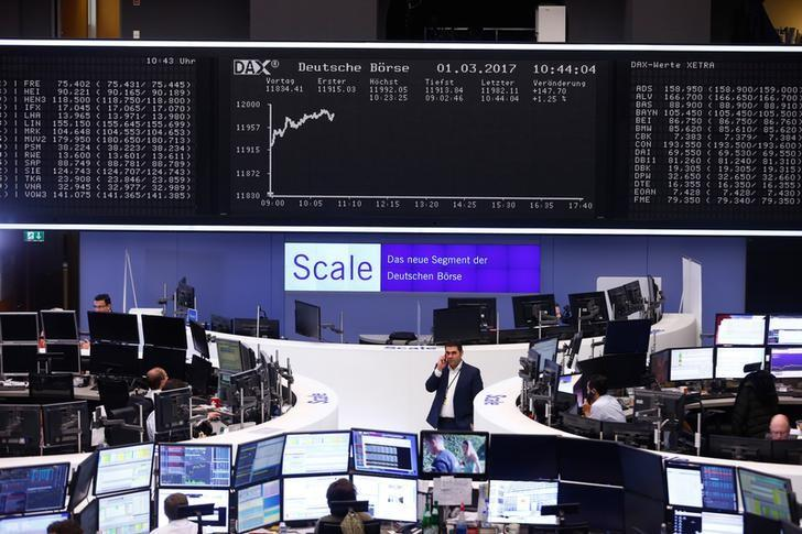 Traders work at their desks in front of the German share price index, DAX board, at the stock exchange in Frankfurt, Germany, March 1, 2017. REUTERS/Ralph Orlowski