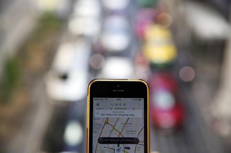 A phone running the Uber application is held above the traffic in central Bangkok December 10, 2014.  REUTERS/Damir Sagolj
