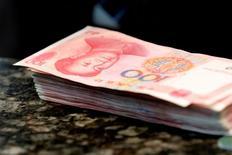 Купюры валюты юань в банке в Пекине 30 марта 2016 года. Citigroup Inc во вторник сообщил, что включит гособлигации материкового Китая в свои индексы развивающихся рынков и региона, что знаменует очередную победу для Пекина, пытающегося привлечь иностранных инвесторов на свой долговой рынок для борьбы с оттоком капитала. REUTERS/Kim Kyung-Hoon/File Photo