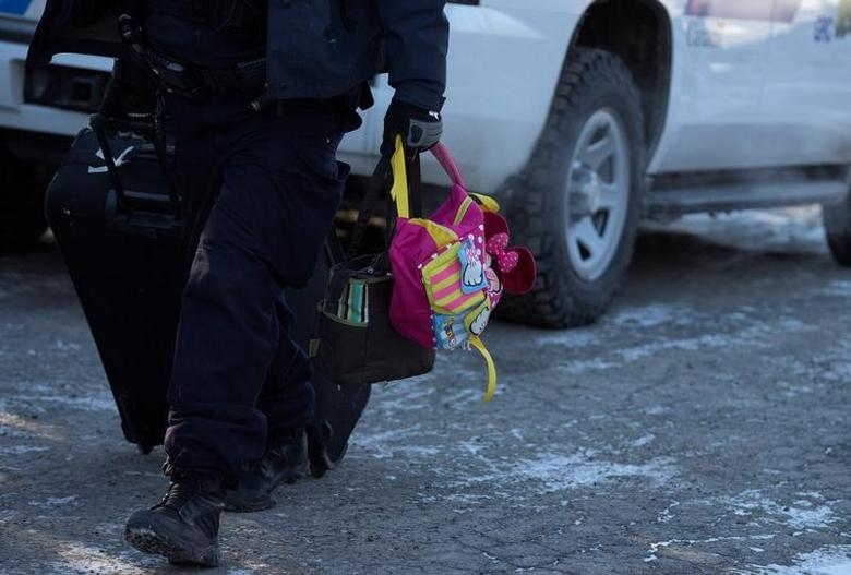 A Royal Canadian Mounted Police (RCMP) vehicle carries luggage after detaining a family that said they were from Yemen for crossing the U.S.-Canada border into Hemmingford, Quebec, Canada March 5, 2017.  REUTERS/Christinne Muschi