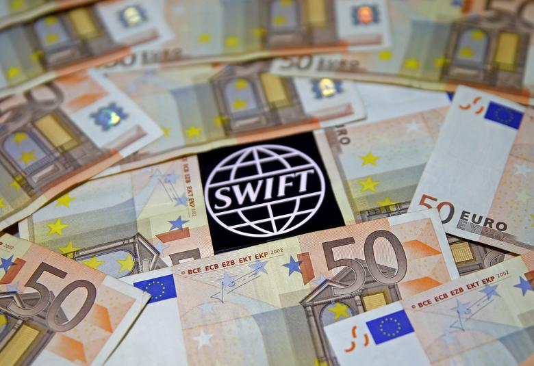 FILE PHOTO: Swift code bank logo is displayed on an iPhone 6s among Euro banknotes in this picture illustration January 26, 2016.  REUTERS/Dado Ruvic/File Photo