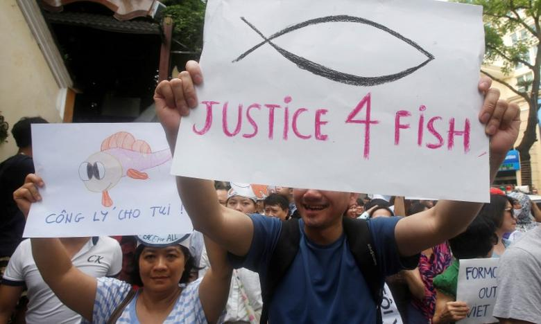 Demonstrators, holding signs, say they are demanding cleaner waters in the central regions after mass fish deaths in recent weeks, in Hanoi, Vietnam May 1, 2016. REUTERS/Kham/File Photo