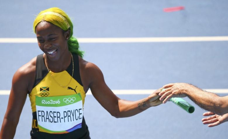 2016 Rio Olympics - Athletics - Preliminary - Women's 4 x 100m Relay Round 1 - Olympic Stadium - Rio de Janeiro, Brazil - 18/08/2016. Shelly-Ann Fraser-Pryce (JAM) of Jamaica hands back the baton. REUTERS/David Gray