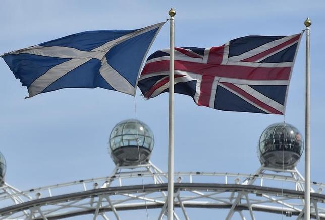 3月9日、英国のメイ首相の報道官によると同首相は、スコットランドの独立の是非を問う2度目の住民投票は必要ないとの考えだ。写真はスコットランドと英国の旗。ロンドンで2014年8月撮影(2017年 ロイター/Toby Melville)