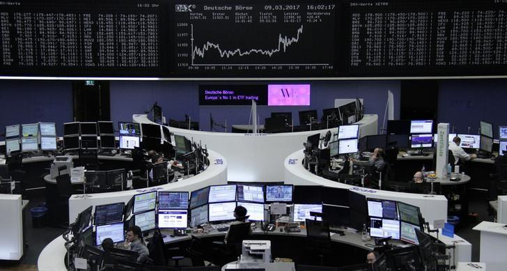 Traders work at their desks in front of the German share price index, DAX board, at the stock exchange in Frankfurt, Germany, March 9, 2017. REUTERS/Staff/Remote