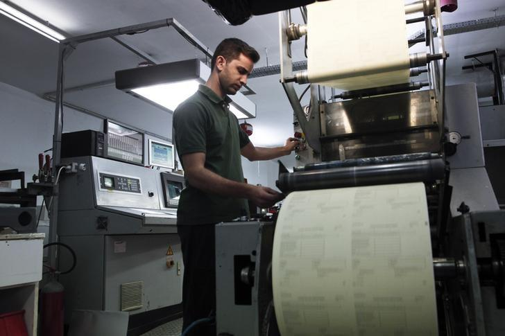 An employee operates a printing machine at the factory of ''Typorganosi S.A'' company in northwestern Athens November 12, 2014.   REUTERS/Alkis Konstantinidis/Files