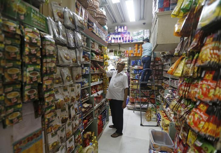 Employees work inside a grocery store at a residential area in Mumbai, India, March 14, 2016. REUTERS/Shailesh Andrade/Files