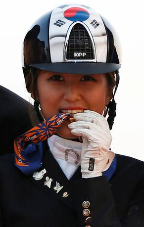 South Korea's Chung Yoo-ra, then known as Chung Yoo-yeon, bites her gold medal as she poses after winning the equestrian Dressage Team competition at the Dream Park Equestrian Venue during the 17th Asian Games in Incheon September 20, 2014. REUTERS/Kim Hong-Ji/Files
