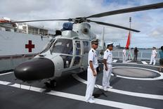 FILE PHOTO: Members of the Chinese People Liberation Army Navy stand by a helicopter on the PLA(N) ship Haikou as it sits docked at Joint Base Pearl Harbor Hickam in Honolulu, Hawaii, July 5, 2014.  REUTERS/Hugh Gentry/File Photo