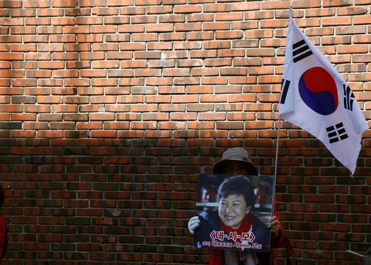 A supporter of South Korea's ousted leader Park Geun-hye holding Park's photo and the national flag stands outside her private home in Seoul, South Korea, March 15, 2017. REUTERS/Kim Kyung-Hoon