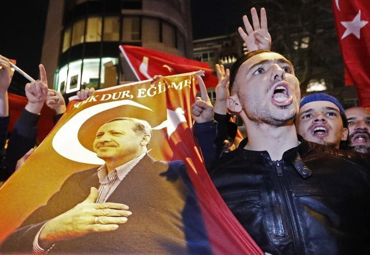 Demonstrators with banners of Turkish President Recep Tayyip Erdogan gather outsidethe Turkish consulate to welcome the Turkish Family Minister Fatma Betul Sayan Kaya, who decided to travel to Rotterdam by land after Turkish Foreign Minister Mevlut Cavusoglu's flight was barred from landing by the Dutch government, in Rotterdam, Netherlands March 11, 2017.      REUTERS/Yves Herman/Files