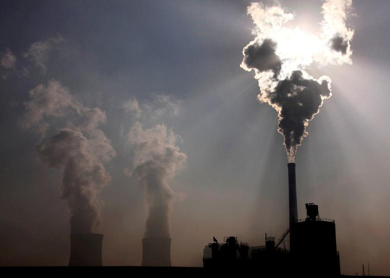 FILE PHOTO: A coal-burning power plant can be seen behind a factory in the city of Baotou, in China's Inner Mongolia Autonomous Region October 31, 2010.     REUTERS/David Gray/File Photo