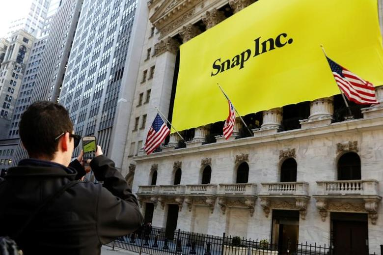 A man takes a photograph of the front of the New York Stock Exchange (NYSE) with a Snap Inc. logo hung on the front of it shortly before the company's IPO in New York, U.S., March 2, 2017.  REUTERS/Lucas Jackson