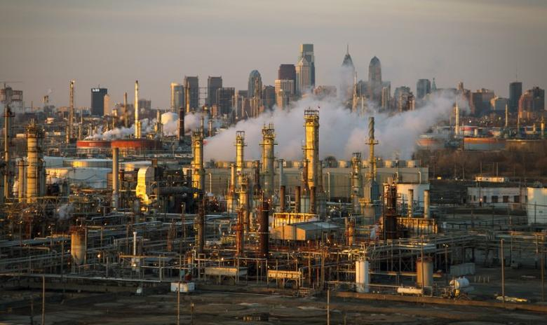 The Philadelphia Energy Solutions oil refinery owned by The Carlyle Group is seen at sunset in front of the Philadelphia skyline March 24, 2014. Picture taken March 24, 2014. REUTERS/David M. Parrott/File Photo