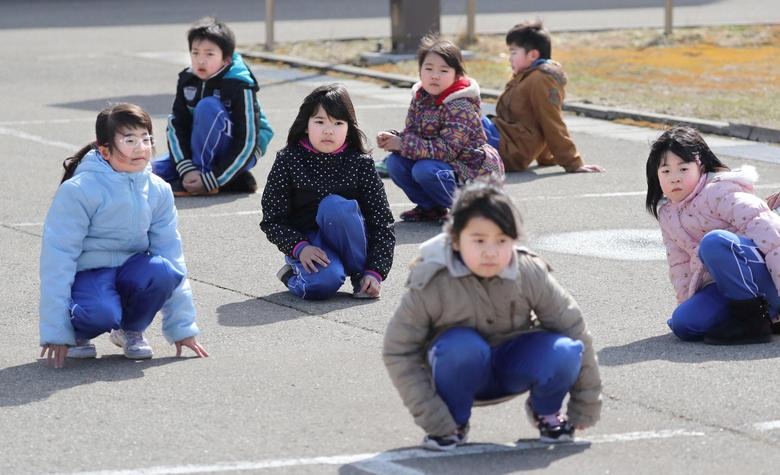 Elementary school students squat down on the street as they participate in an evacuation drill for local residents based on the scenario that a ballistic missile launched landed in Japanese waters, in Oga, Akita prefecture, Japan March 17, 2017.  Kyodo/via REUTERS