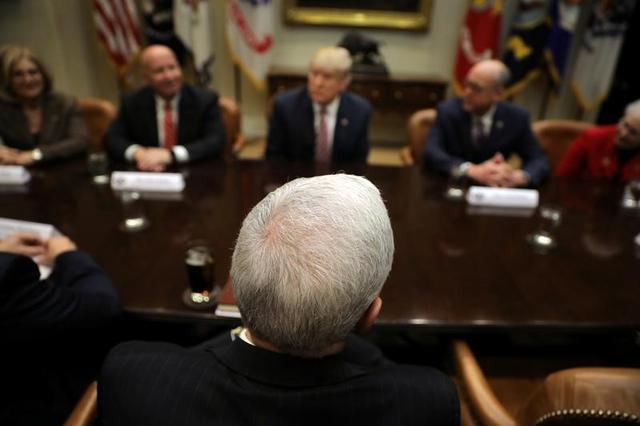 U.S. President Donald Trump (C) and Vice President Mike Pence (bottom) attend a healthcare meeting with key House Committee Chairmen at the White House in Washington, U.S., March 10, 2017.  REUTERS/Carlos Barria