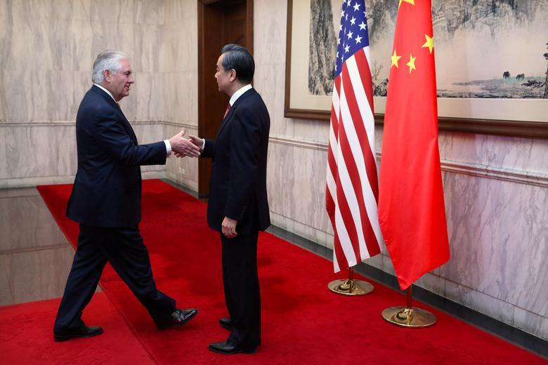 U.S. Secretary of State Rex Tillerson (L) is greeted by Chinese Foreign Minister Wang Yi as he arrives for a bilateral meeting at the Diaoyutai State Guesthouse in Beijing, China, Saturday, March 18, 2017. REUTERS/Mark Schiefelbein/Pool