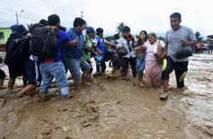سكان يعبرون شارعا غمرته مياه الفيضانات في تروجيلو شمال بيرو يوم الجمعة. تصوير: دوجلاس جوريز - رويترز. (تستخدم الصورة في الأغراض التحريرية فقط ولا يجوز اعادة بيعها أو الاحتفاظ بها في أرشيف)