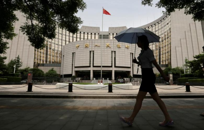 FILE PHOTO: A woman walks past the headquarters of the People's Bank of China (PBOC), the central bank, in Beijing, China June 21, 2013.   REUTERS/Jason Lee/File Photo