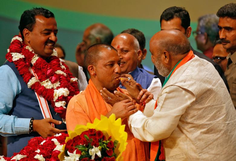 India's ruling Bharatiya Janata Party (BJP) leader Yogi Adityanath (C) is offered sweets after he was elected as Chief Minister of India's most populous state of Uttar Pradesh, during the party lawmakers' meeting in Lucknow, India March 18, 2017. REUTERS/Pawan Kumar