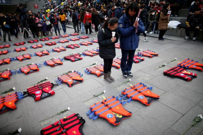 A mother prays with her daughter in front of life vests symbolising the 304 victims of sunken ferry Sewol during a protest demanding South Korean President Park Geun-hye's resignation in Seoul, South Korea December 17, 2016.  REUTERS/Kim Hong-Ji - RTX2VFKR