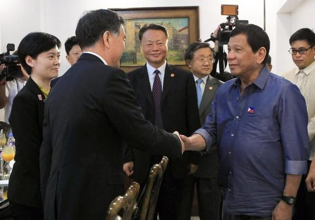 Philippine President Rodrigo Duterte greets Vice Premier of China, Wang Yang (L) during his courtesy call at the Presidential Guest House in Davao city, Philippines March 17, 2017.  Malacanang Photo/Handout via Reuters