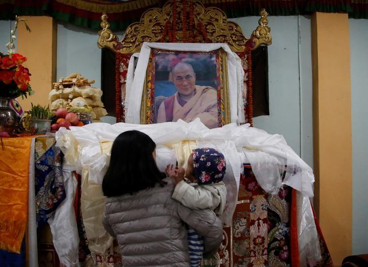 A Tibetan woman carrying a child offers prayer on the portrait of exiled Tibetan spiritual leader, the Dalai Lama, during a function to mark the Tibetan Uprising Day at the Tibetan Refugee camp in Lalitpur, Nepal March 10, 2017. REUTERS/Navesh Chitrakar