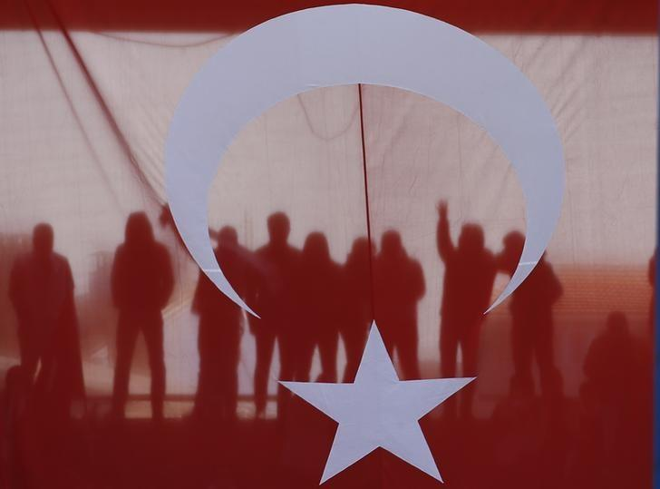 People are seen through a Turkish flag during a ceremony marking the 102nd anniversary of Battle of Canakkale, also known as the Gallipoli Campaign, in Canakkale, Turkey, March 18, 2017. REUTERS/Osman Orsal