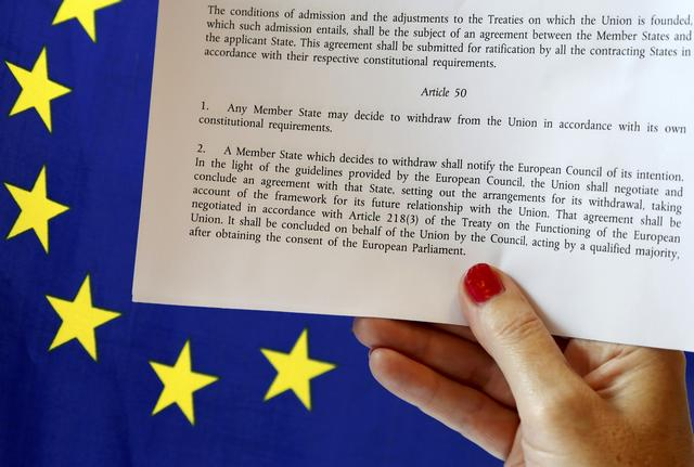 FILE PHOTO - Article 50 of the EU's Lisbon Treaty that deals with the mechanism for departure is pictured near an EU flag following Britain's referendum results to leave the European Union, in this photo illustration taken in Brussels, Belgium, June 24, 2016. REUTERS/Francois Lenoir/Illustration/File Photo